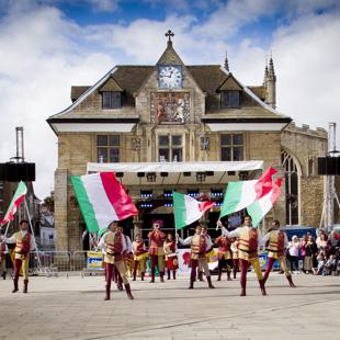 Performers waving Italian flags in Peterborough market square