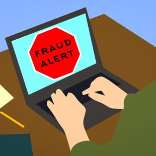 Person sitting at laptop with a fraud alert message on screen